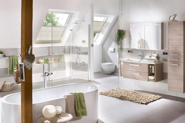 Nur ein einzelner Eichenholzpfosten des Dachstuhls erinnert an den ehemaligen Dachboden: Hier erstrahlt heut ein lichtdurchflutetes Bad mit großzügigen Dachfenstern. Foto: Velux Deutschland GmbH