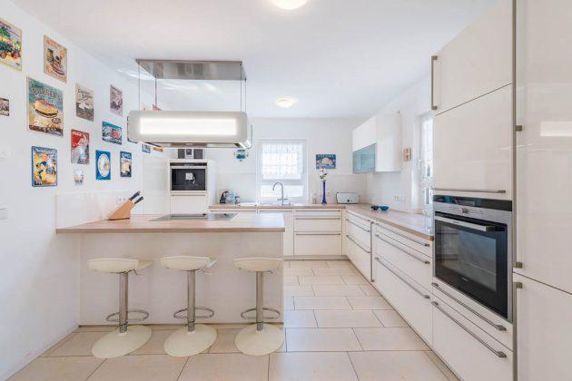 Die weißen Hochglanzoberflächen verleihen der Küche eine moderne Leichtigkeit.