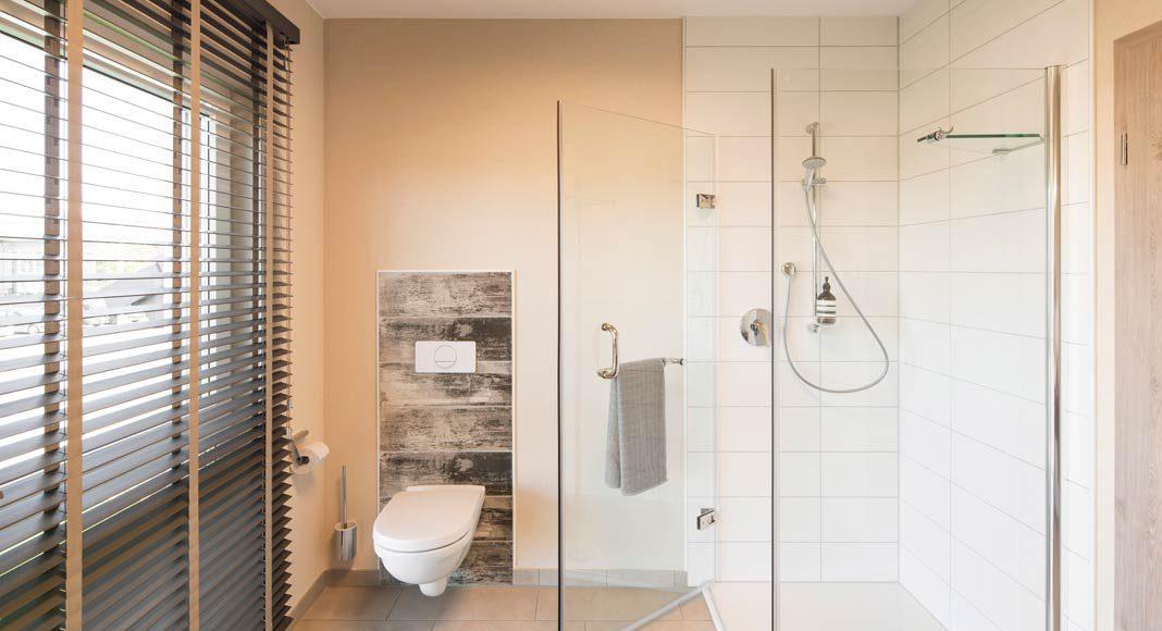Bodenebene Dusche mit Spritzschutz aus Glas bietet rundum angenehmen Komfort im Bad.