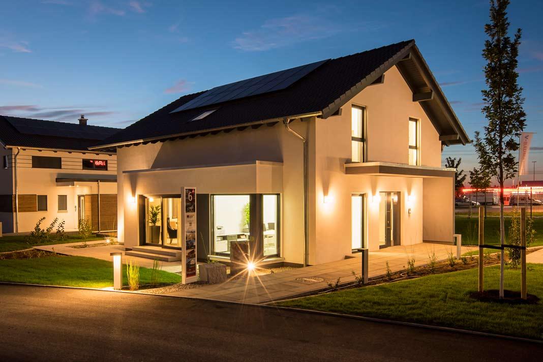 In den Abendstunden zeigt sich das Musterhaus in Günzburg durch die großen Fensterflächen von seiner leuchtenden Seite.