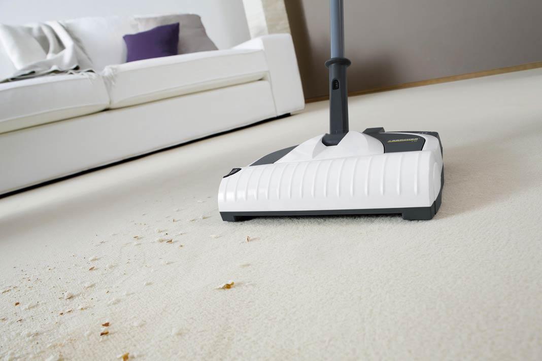 Staubsauger entfernt Schmutz auf Teppich