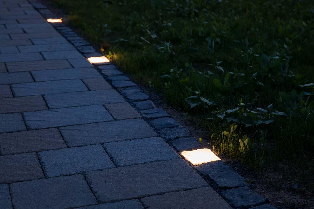 """Leuchtende """"Pflastersteine"""" weisen hier den Weg zum Musterhaus."""