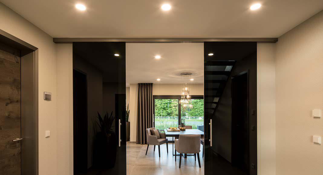 Durch Schiebetüren lässt sich der Wohn-Essbereich von der Diele abtrennen.