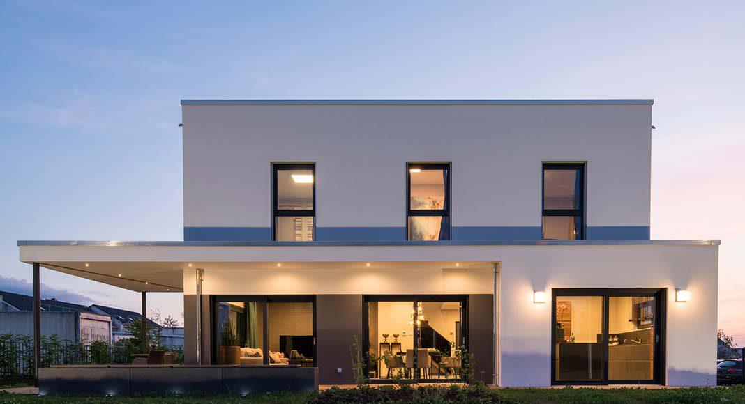 In der Abendstimmung zeigt sich durch die hell erleuchteten Fenster der große Glasanteil des Hauses.