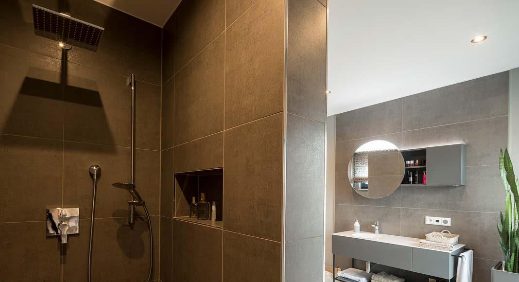 Hinter der Wandscheibe befindet sich die bodenebene XXL-Dusche.
