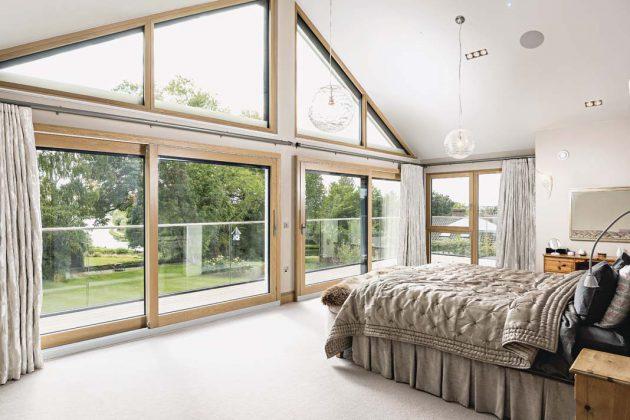Schlafzimmer mit verglastem Giebel und Empfangshalle mit geschwungener Treppe.