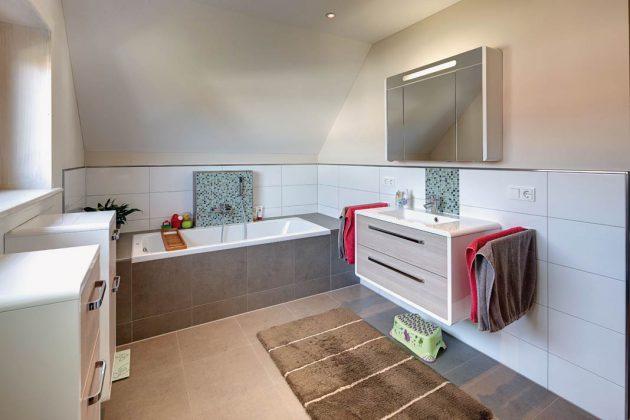 Das Bad zeigt sich auch wohnlich ohne Holz, dank der gedeckten Naturtöne an der Wand und am Boden.