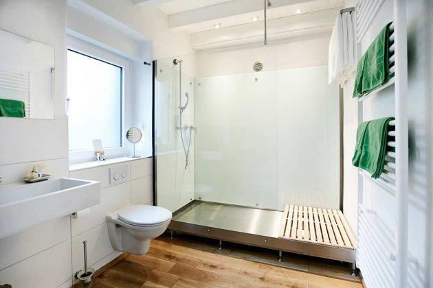 Die puristisch-stylische Edelstahl- und Glaskombination im Bad entstand aus der Not heraus. Nur so konnte ein vernünftiger Bodenablauf hergestellt werden.