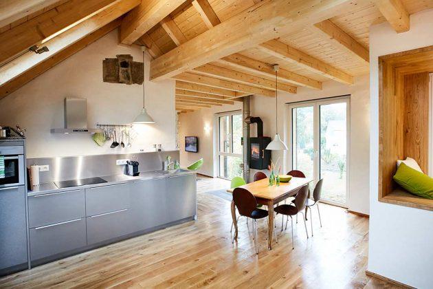 Modernes Wohnen in alten Gemäuern mit Edelstahlküche und wandhängendem Kaminofen.