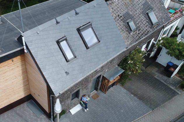 Edelstahl-Kaminschornstein, weißes Rohr am Dach und Antennenstange mit Halteseilen.