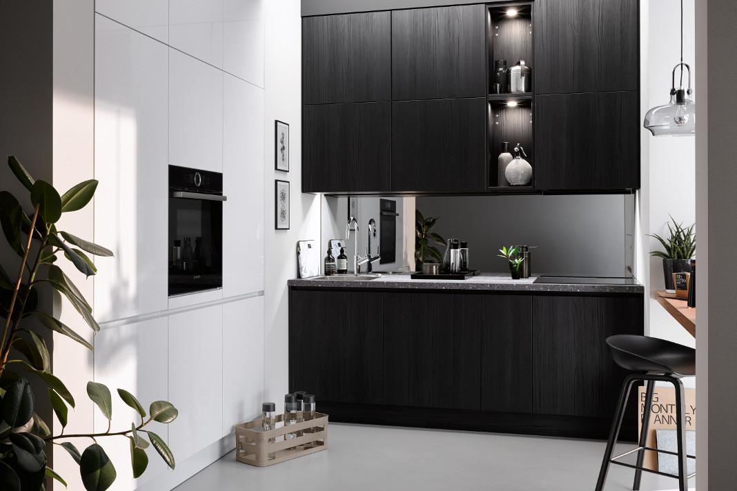 Moderne Küche mit grifflosen Fronten und Backofen auf Arbeitshöhe.