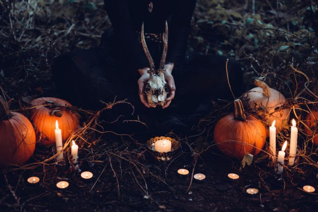 gruselige Halloween Dekoration mit Kerzen und Skelett in schwarz