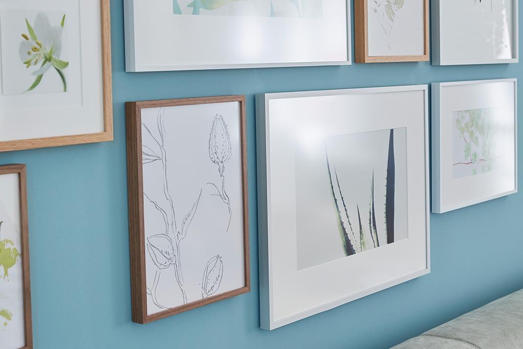 Blaue Wand mit Bildern und Passepartout.