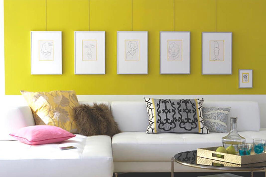 Wohnzimmer mit gelber Wand und Bilderrahmen in gleichem Abstand