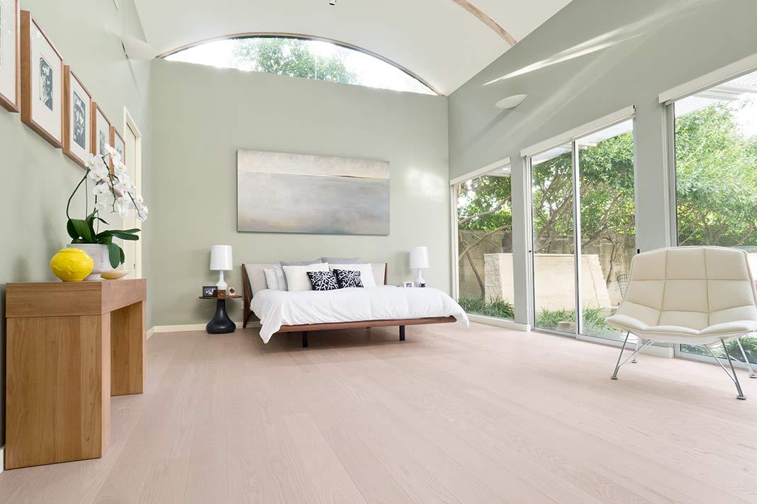 Nutholzboden aus Esche in Schlafzimmer mit bodentiefen Fenstern.