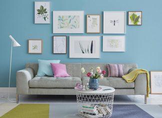 Wohnzimmer mit blauer Wand und Bildern in Bilderahmen