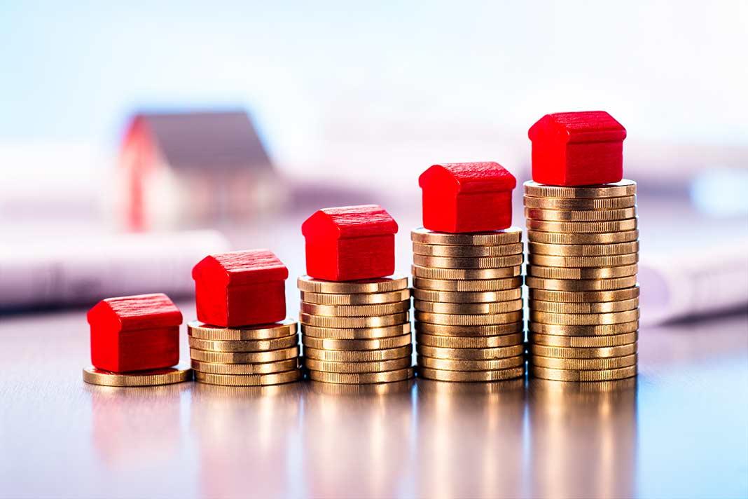 Kleine Häsuer stehen auf aufgestapelten Münzen