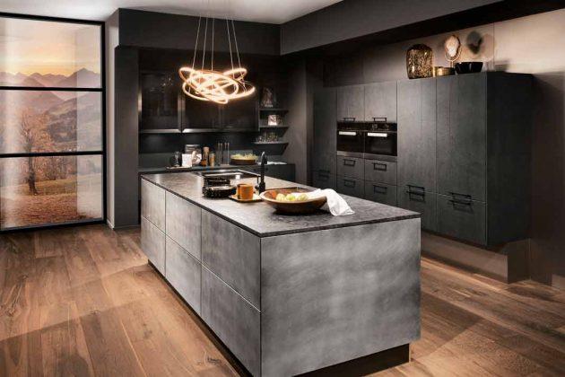 Schwarze Küche mit Kücheninsel in Betonoptik und Holzfußboden
