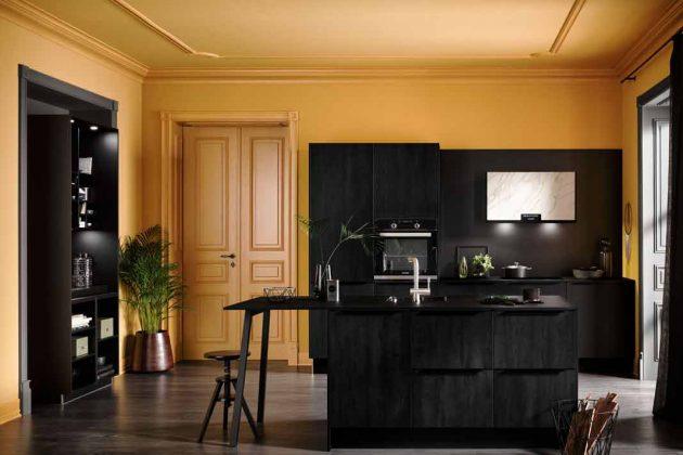 Schwarze Küche mit gelben Wänden.