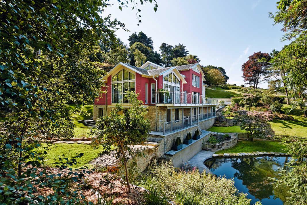 Zwei Stile in einem Einfamilienhaus: Naturstein und Holzhaus mit großen Fensterflächen - Baufritz GmbH & Co. KG