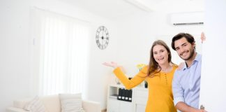 Homestory Junges Paar heißt Gäste an der Tür seines neuen Hauses willkommen