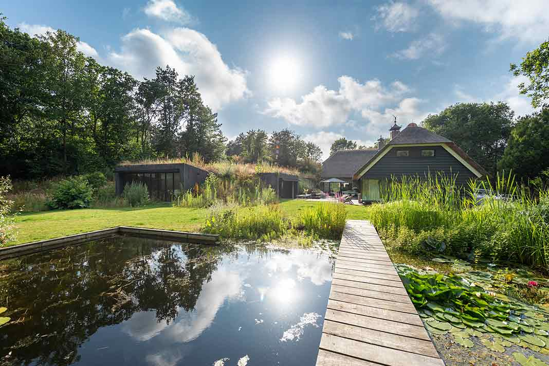 Einfamilienhaus mit Reetdach mit Teich im Garten.