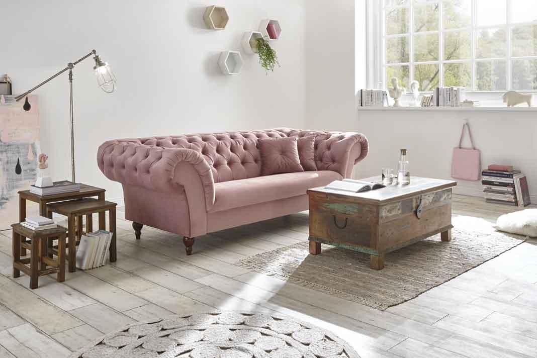 rosa Sofa mit Holzmöbeln