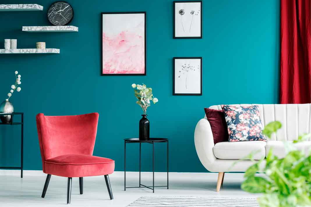 roter Sessel mit hellem Sofa und blauer Wand