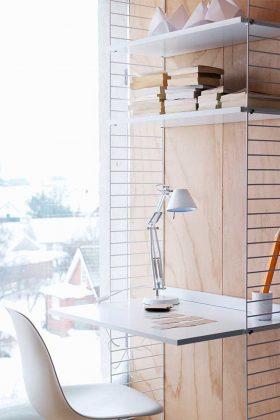 Schreibtisch mit Lampe an einem Fenster.