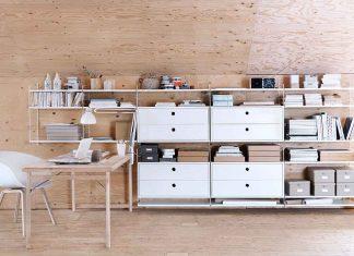 String Works Regalsystem mit Schreibtisch vor einer Holzwand.
