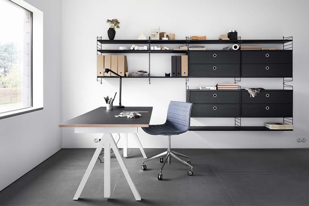 Höhenverstellbbarer Schreibtisch mit ergonomischem Bürostuhl vor Regalsystem
