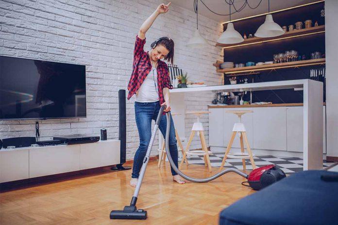 Frau putzt mit Staubsauger und tanzt dabei durchs Wohnzimmer.