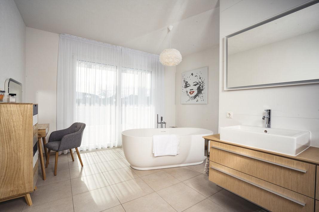 Bad mit freistehender Badewanne in Villa als Architektenhaus im Bauhausstil - WeberHaus