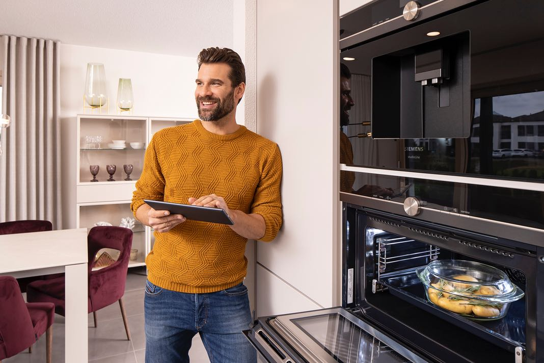 Mann mit Tablet in der Küche steuert sein Smart-Home-System.