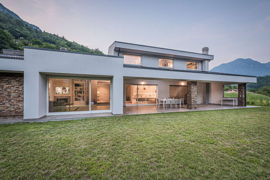Modernes Bauhaus Einfamilienhaus mit Veranda im Abendlicht.
