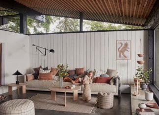Wohnzimmer Hygge mit Sofaldnaschaft und vielen Kissen in gedeckten Farbtönen.