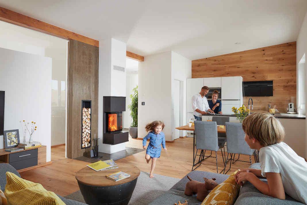 Wohnzimmer mit Schiedel Kingfire Kamin mit vierköpfiger Familie.