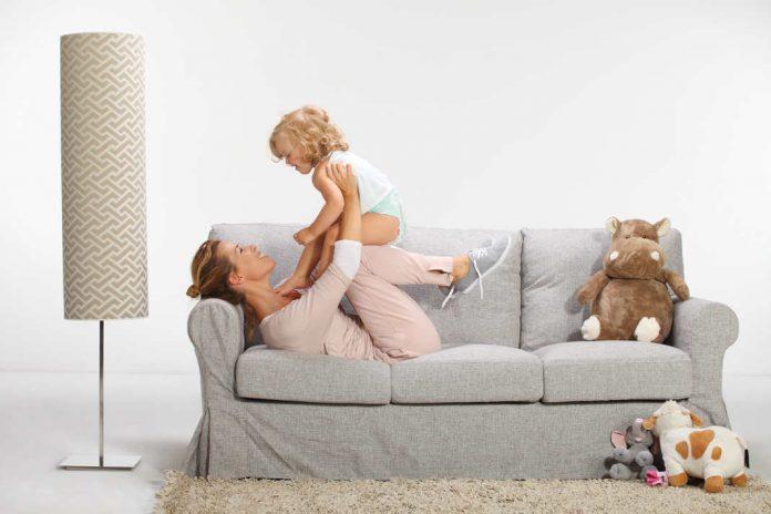 Haus kindersicher machen Mutter mit Baby auf dem Sofa