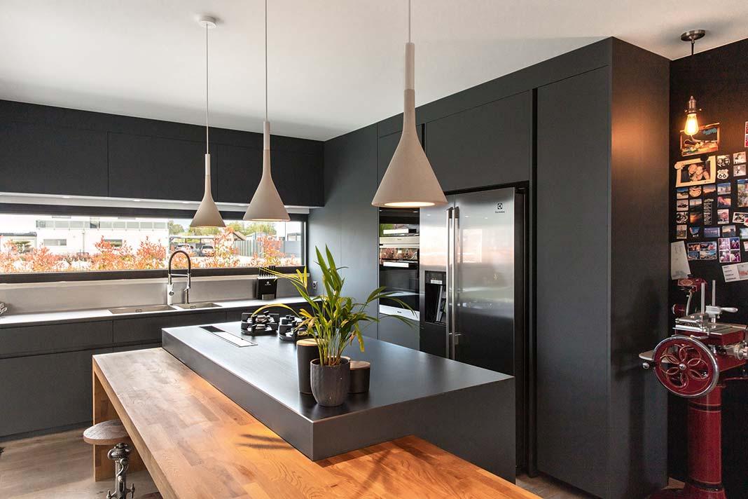 Küche mit grauen Elementen, die durch einen Holztisch abergundet wird