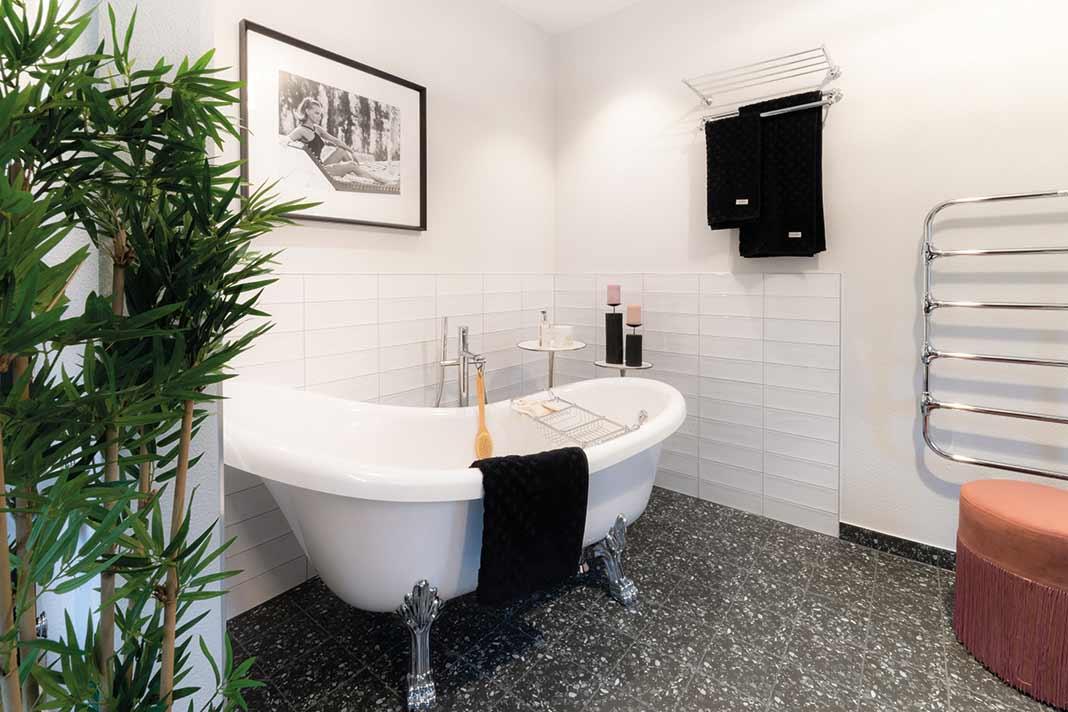 Badezimmer mit ovaler Badewanne und Fliesenspiegel als Spritzschutz
