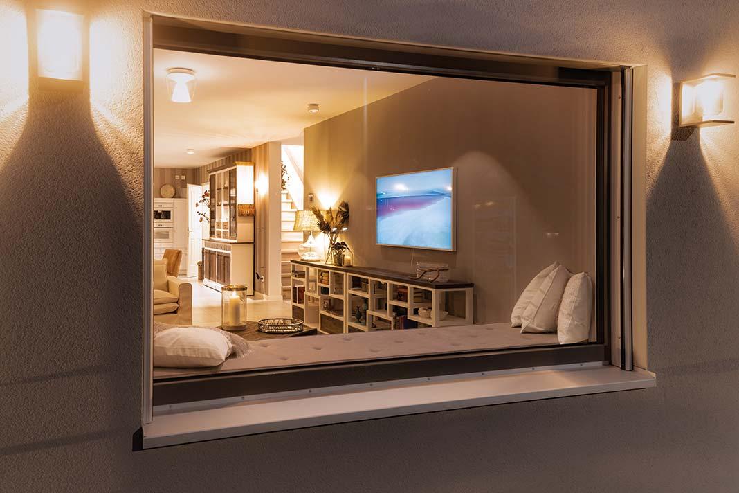 Großes Fenster mit Sitzbank im Innenraum, angrenzend an Wohnraum