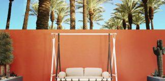 Moderne Hollywoodschaukel vor roter Wand an einem Pool.