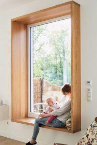 Cocooning: Frau mit Baby in einem Sitzfenster mit Blick in den Garten.