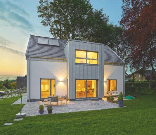 Einfamilienhaus mit beleuchteten Fenstern in der Abendsonne.