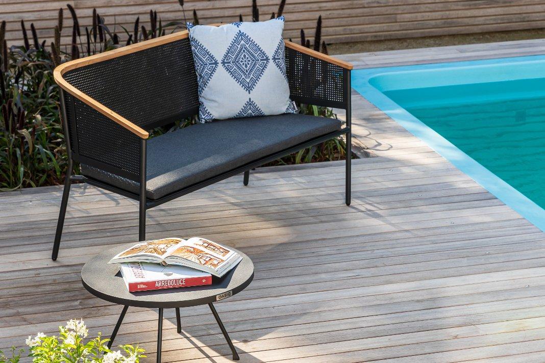 Garten Loungemöbel Gartensofa mit Sitzpolster und Kissen neben einem Pool.