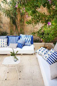 Garten Loungemöbel Outdoor-Sofa mit blau-weißen Kissen.