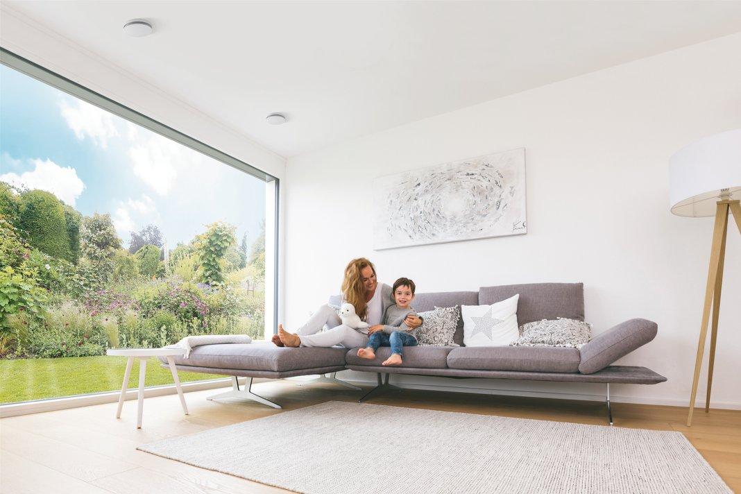 Mutter und Kind auf einem Sofa in einem lichtdurchfluteten Wohnzimmer.