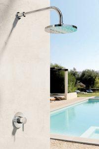 Gartendusche an der Wand neben einem Pool.