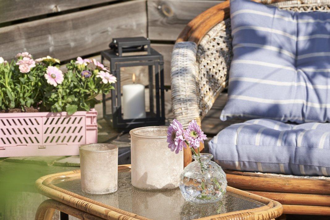 Hygge Garten Sofa mit Beistelltisch und Kerzen.