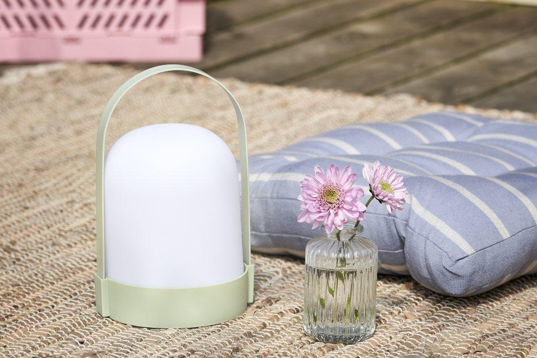 Hygge Garten mit mobiler LED-Lampe auf einem Outdoor-Teppich.